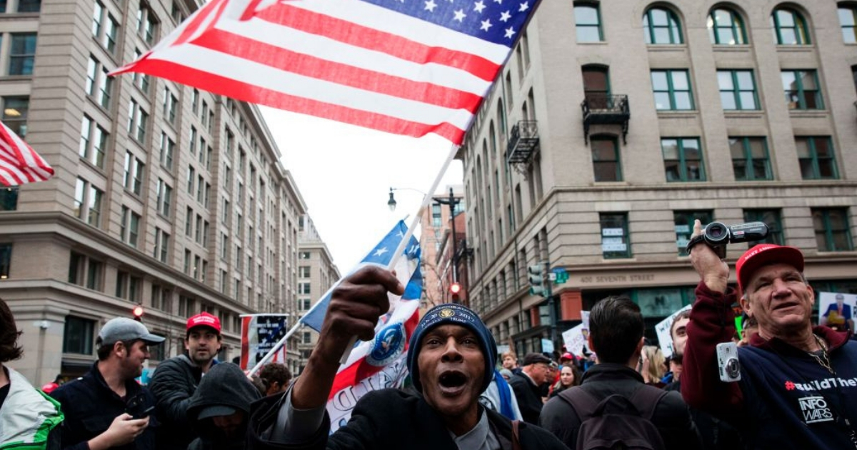 A black man waves a flag in support of President Donald Trump during Trump's inauguration in January 2017