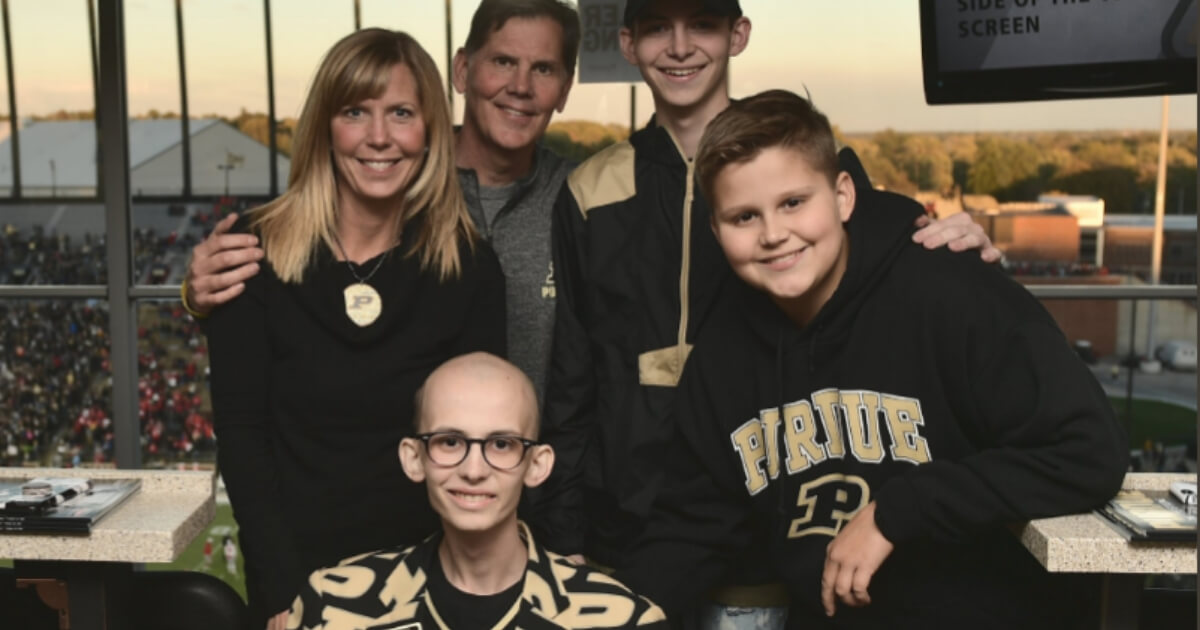 Tyler Trent, seated, poses with his family in a private suite prior to watching Purdue's upset over No. 2 Ohio State on Saturday.