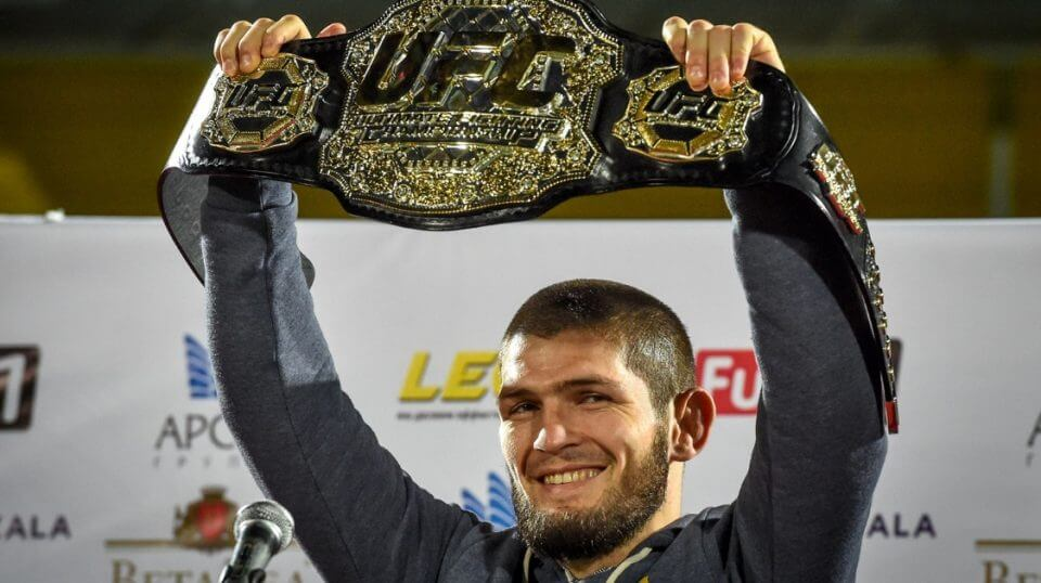 UFC lightweight champion Khabib Nurmagomedov of Russia raises his belt upon arriving in Makhachkala on Monday.
