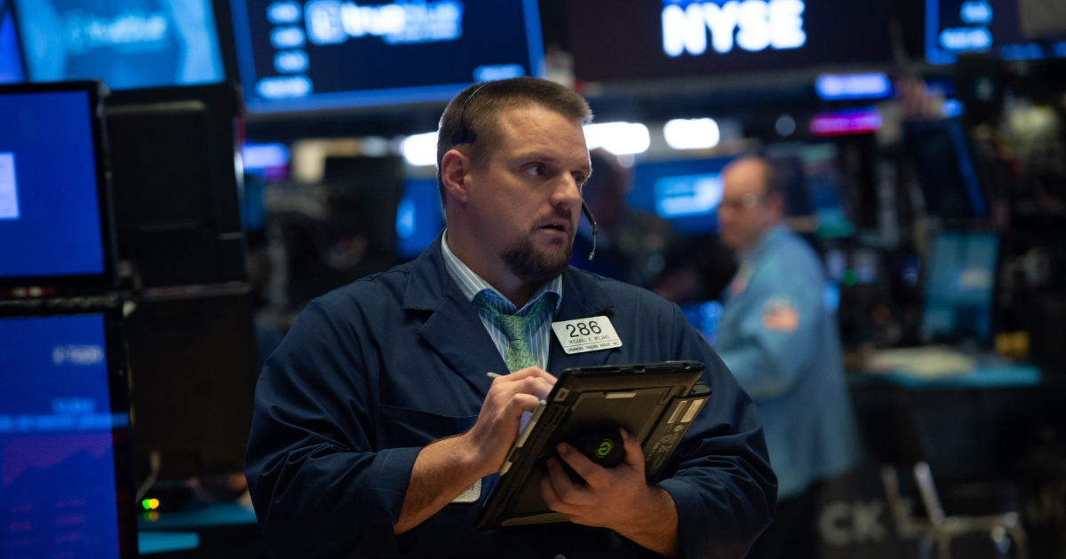 Traders work the floor at the closing bell of the Dow Industrial Average