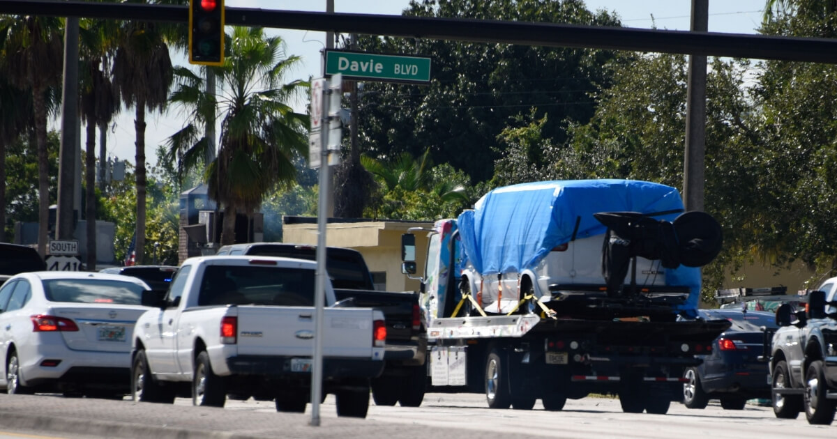 A van covered in blue tarp is towed by FBI investigators on Friday in Plantation, Florida, in connection with the 12 suspicious packages mailed to top Democrats.