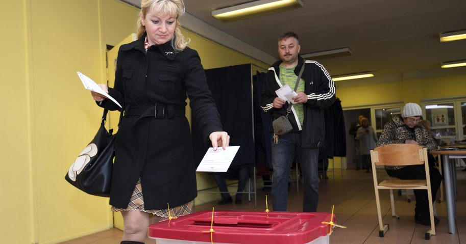 A Latvian woman casts her ballot papers at a polling station in Riga, Latvia