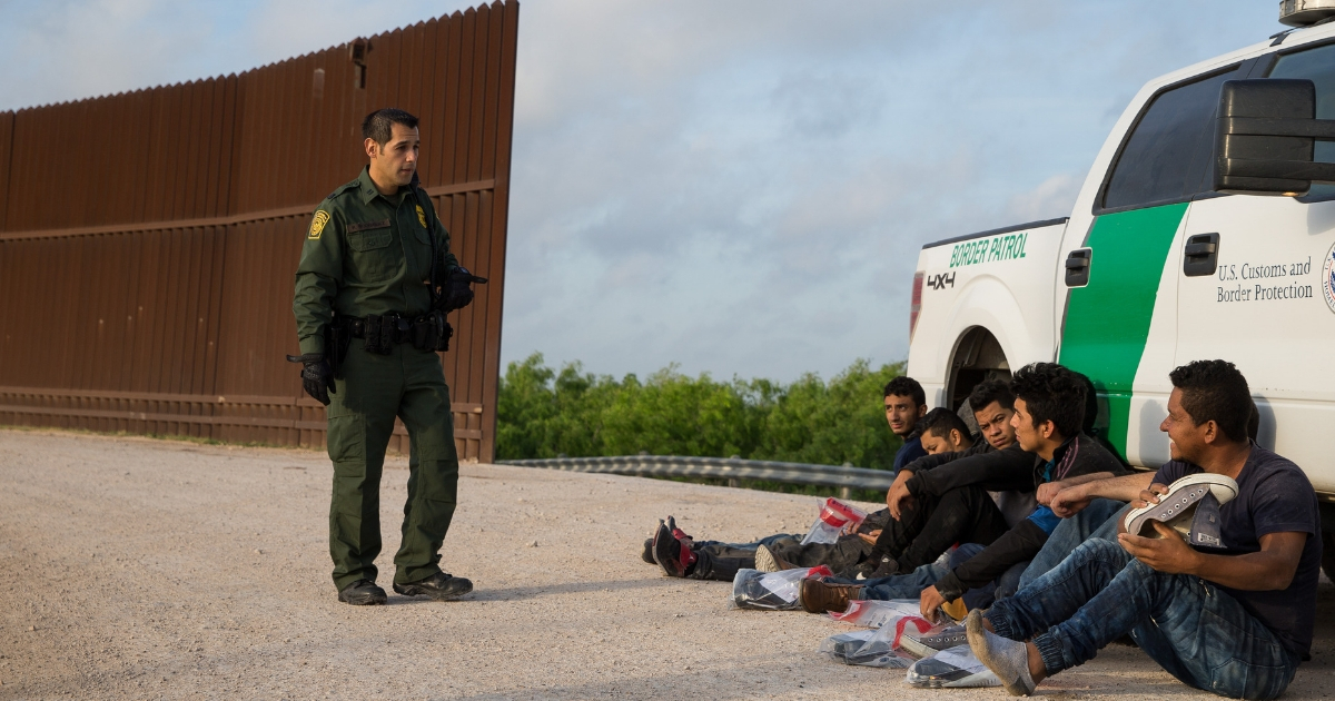 A Border Patrol agent apprehends illegal immigrants