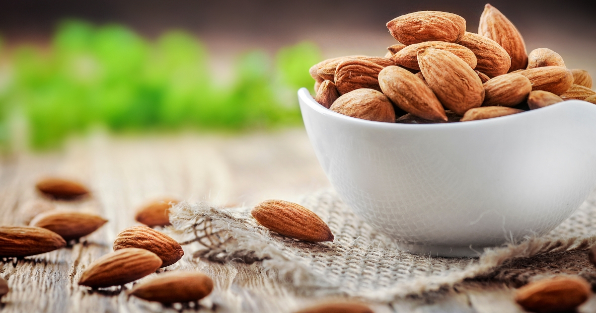 Almonds in a white porcelain bowl on a wooden table.