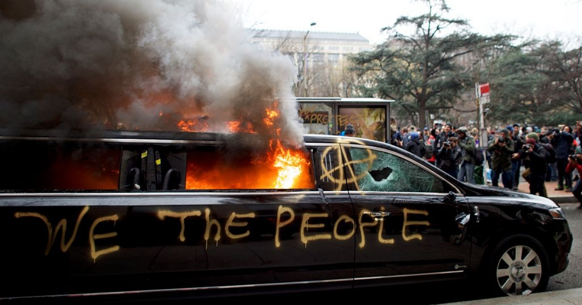 limousine is set aflame with 'We the People' spray painted on the side after the inauguration of Donald Trump.