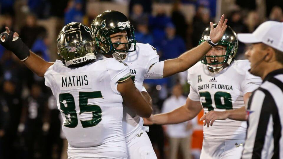 South Florida's Coby Weiss, center, celebrates with teammates Jacob Mathis (85) and Trent Schneider (39) after kicking the go-ahead field goal in a game against Tulsa on Friday night.