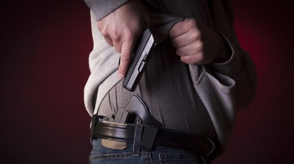 A man drawing a conceal carry pistol from an inside the waistband holster