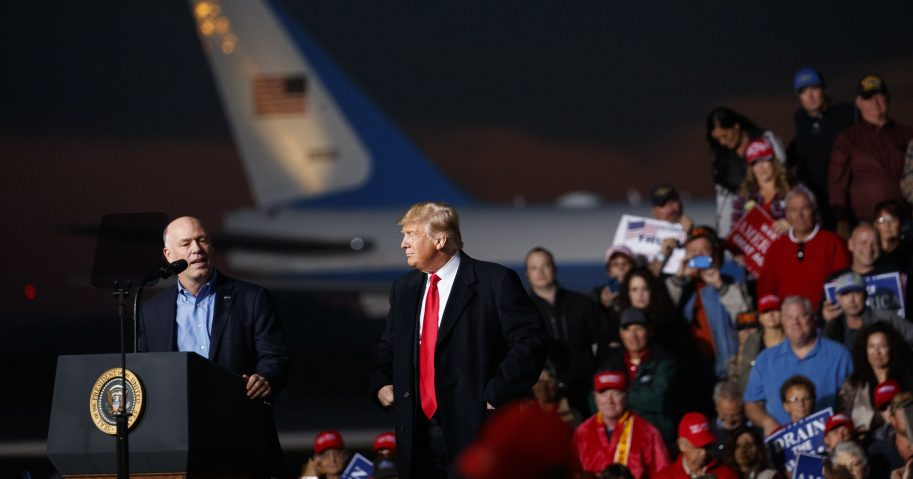 Rep. Greg Gianforte, R-Mont., speaks as President Donald Trump stands right during a campaign rally at Minuteman Aviation Hangar, Thursday, Oct. 18, 2018, in Missoula, Montana.