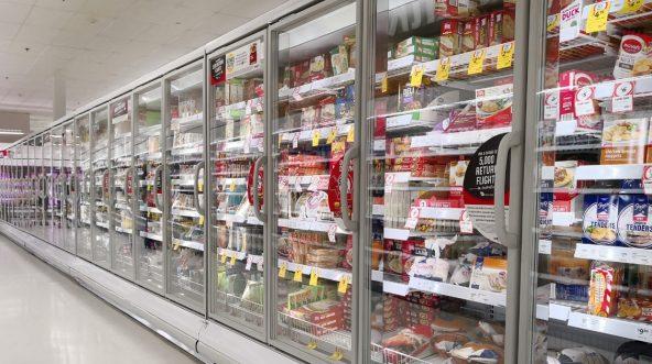 Interior view of huge glass freezer with various brand frozen foods.