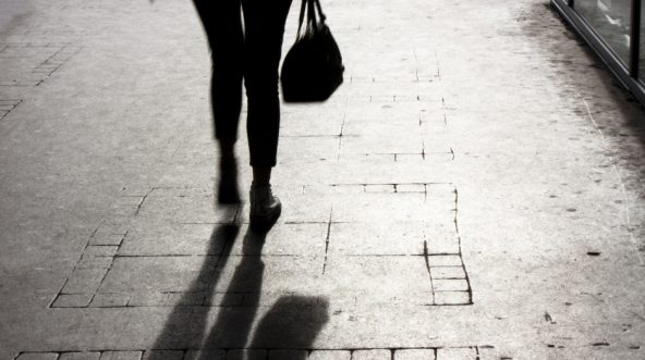 Blurry young woman with a handbag walking alone on city street, in black and white