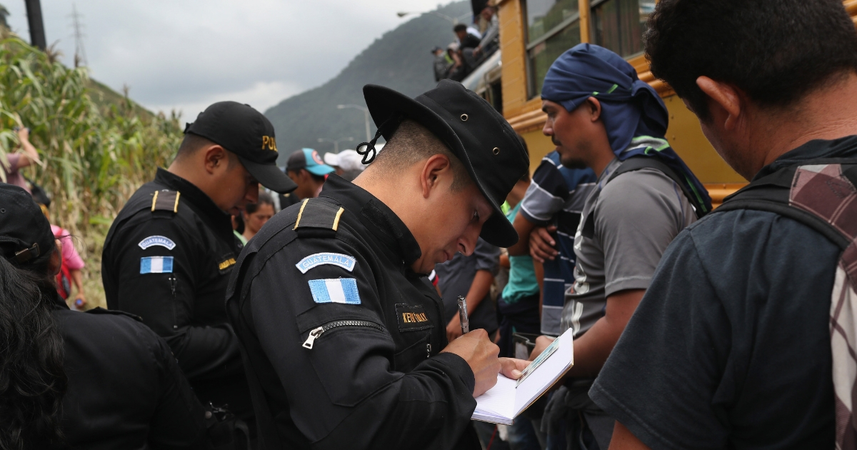 Guatemalan police check immigrants' IDs at a highway checkpoint en route to the border with Mexico.