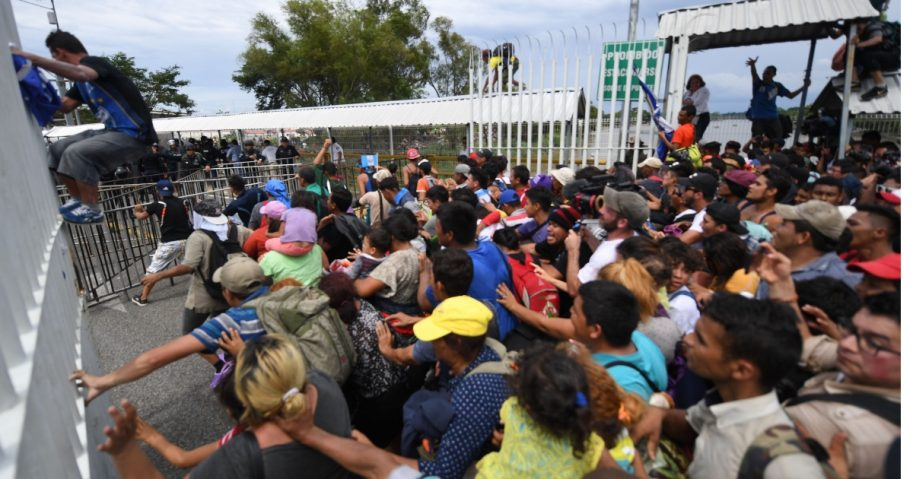 Honduran migrants heading in a caravan to the US, open one of the gates of the Guatemala-Mexico international border bridge.