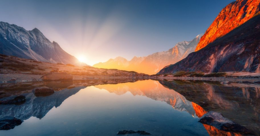 Beautiful landscape with high mountains with illuminated peaks, stones in mountain lake, reflection, blue sky and yellow sunlight in sunrise. Nepal.