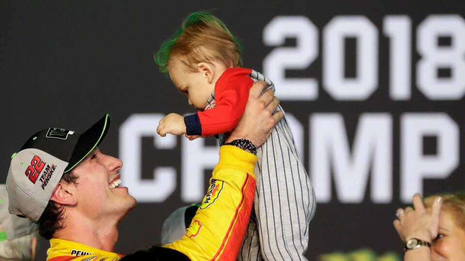 Joey Logano holds his son Hudson after winning the NASCAR Cup Series Championship