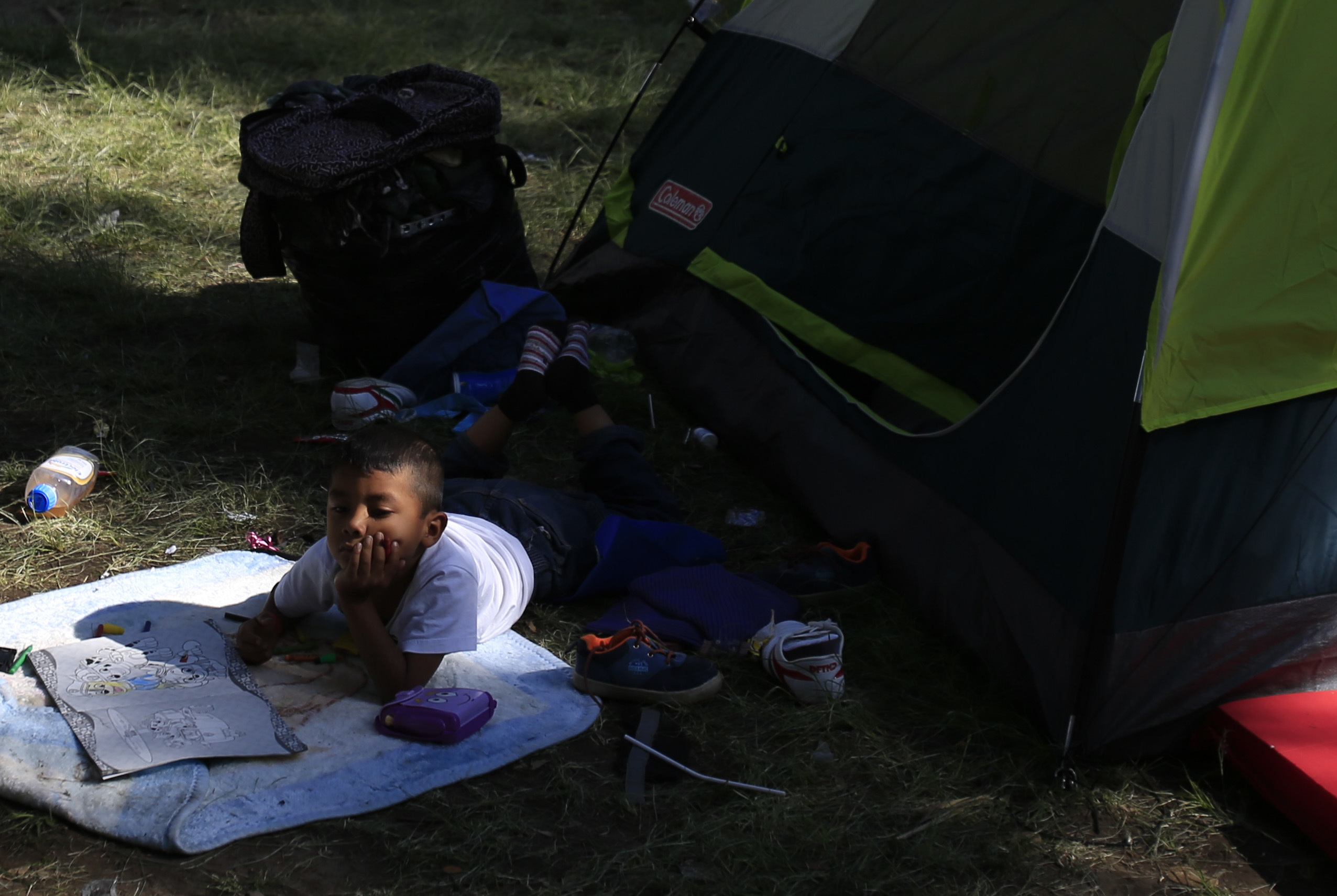 A boy lies with a coloring book outside a tent inside the sports complex where thousands of migrants have been camped out for several days in Mexico City, Friday, Nov. 9, 2018.