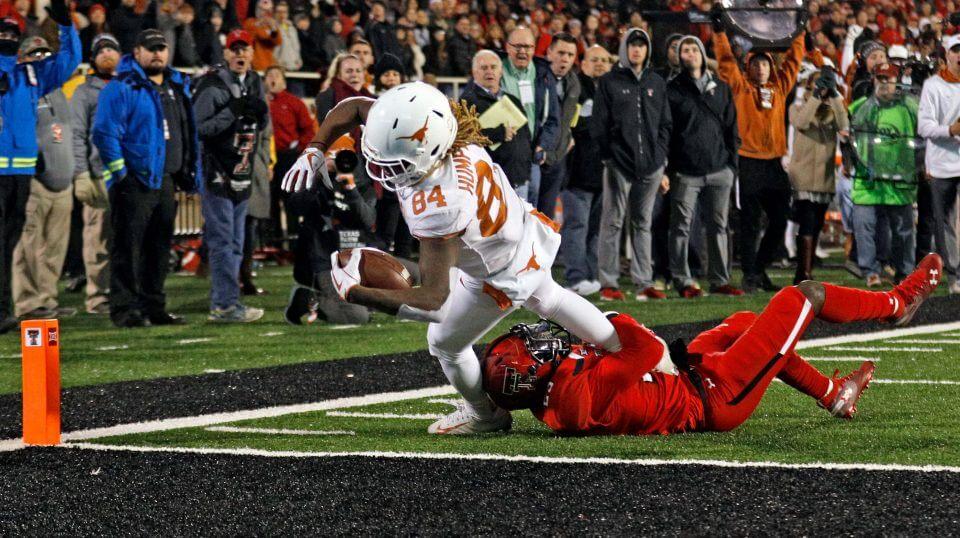 Texas' Lil'Jordan Humphrey (84) scores the game-winning touchdown against Texas Tech's Demarcus Fields (23) Saturday in Lubbock, Texas.