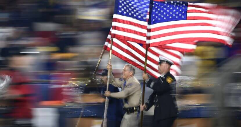 Fire and and law enforcement first responders run with United States flags as they lead players out of the tunnel before the Los Angeles Rams game against the Kansas City Chiefs on Monday night.