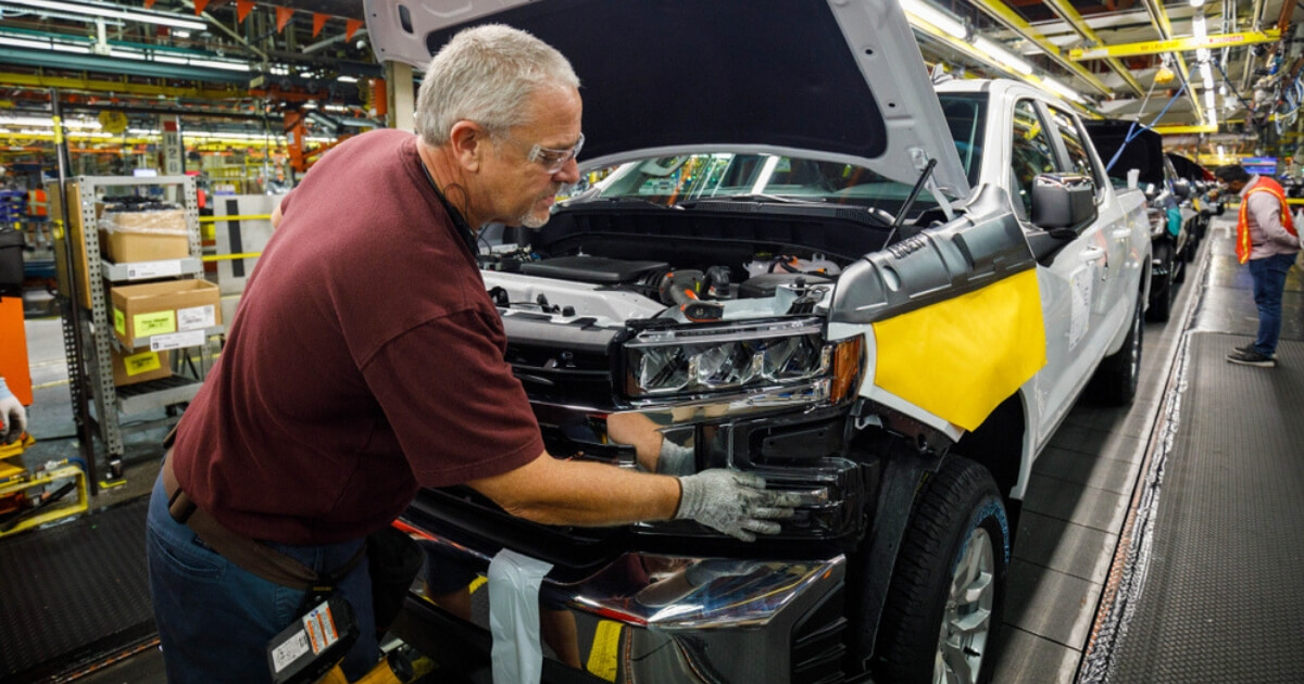A worker attaches a grill at a General Motors pickup truck assembly plant in Indiana.
