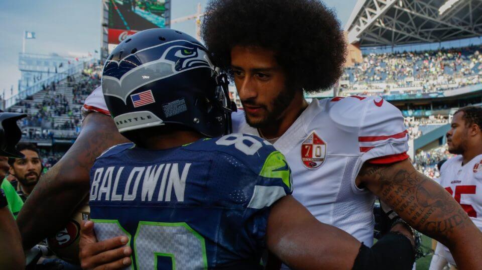 Then-San Francisco 49ers quarterback Colin Kaepernick embraces Seattle Seahawks wide receiver Doug Baldwin after a game Sept. 25, 2016.