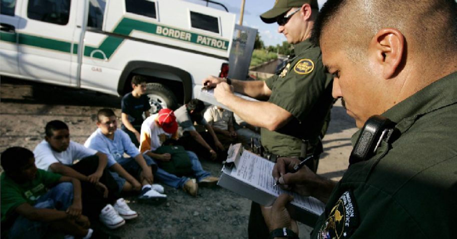 Border patrol agents detain illegal immigrants.