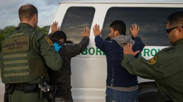 Two Border Patrol agents frisk illegal aliens against a Border Parol van.
