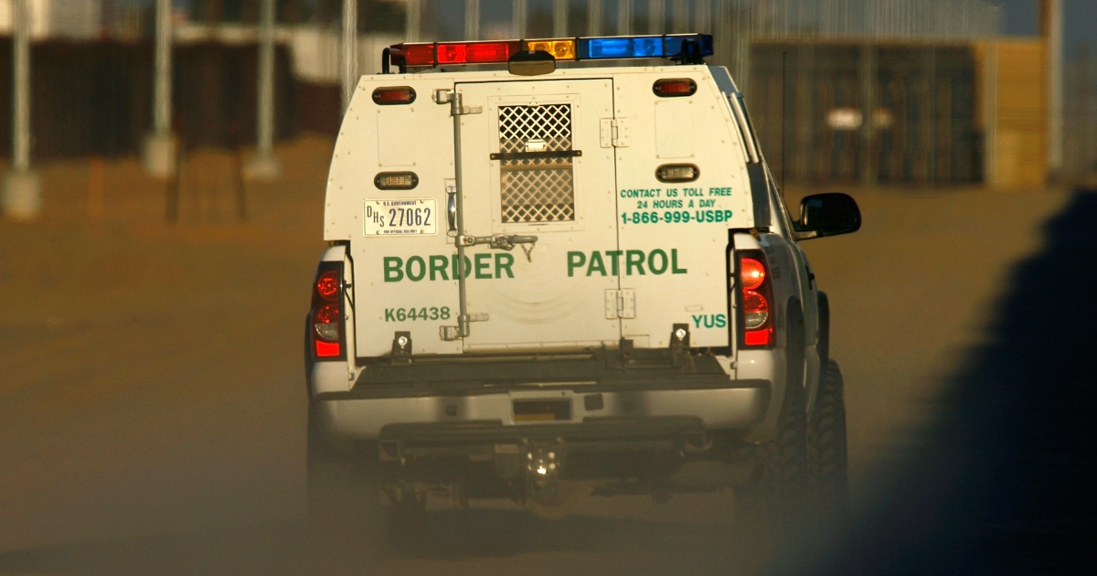A border patrol vehicle drives along a wall of metal that runs along the U.S.-Mexico border.