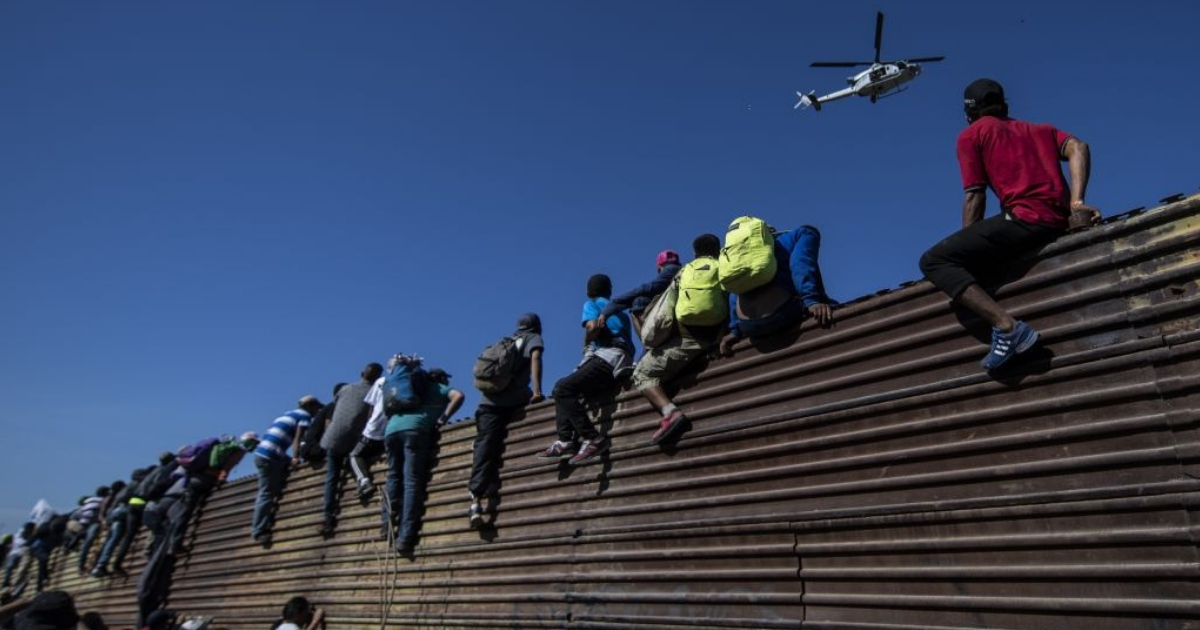 A group of Central American migrants climb a metal barrier on the Mexico-U.S. border.