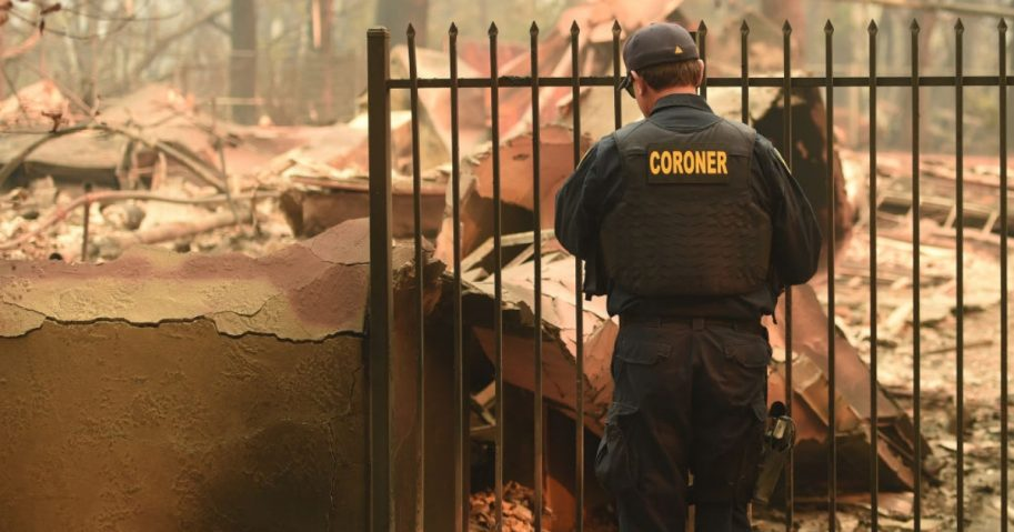 A coroner with the Alameda County Sheriff's Department looks for human remains at a burned residence in Paradise, California