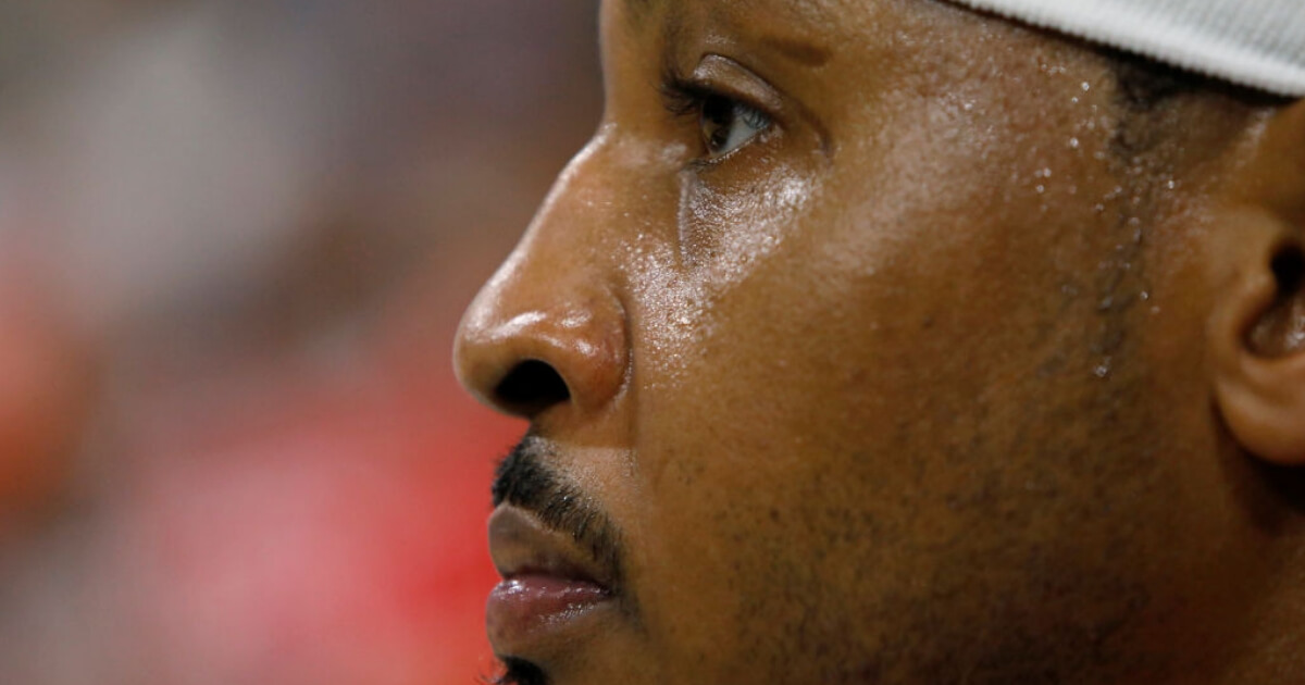 Carmelo Anthony watches the action from the Rockets' bench