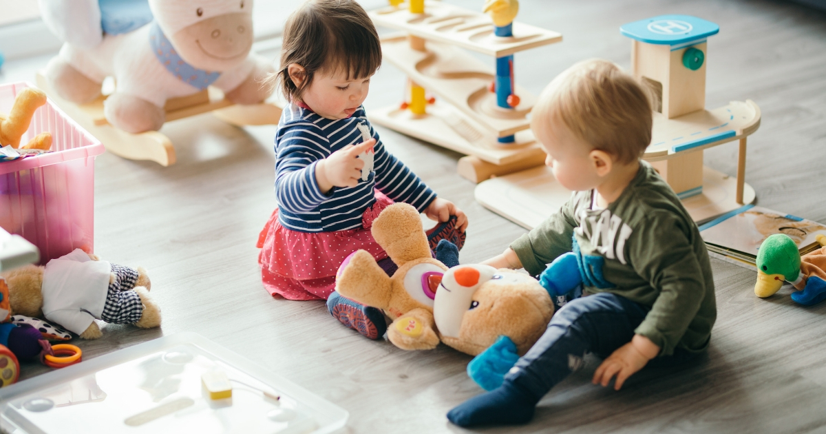 A little girl and a little boy play with toys.