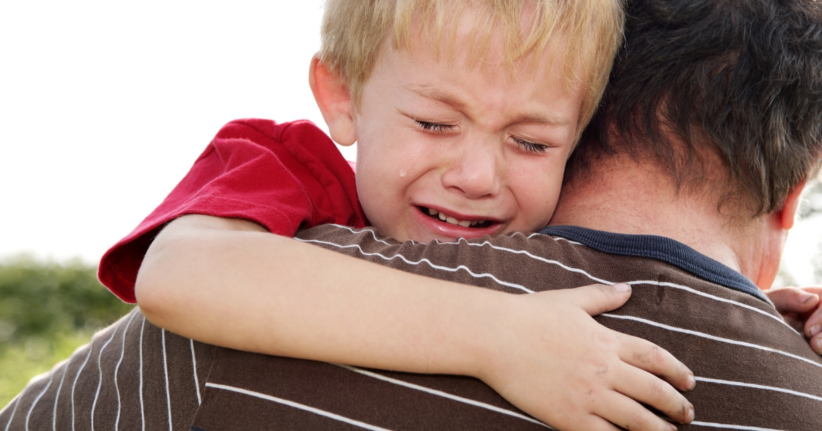 Crying Boy in Father's Arms