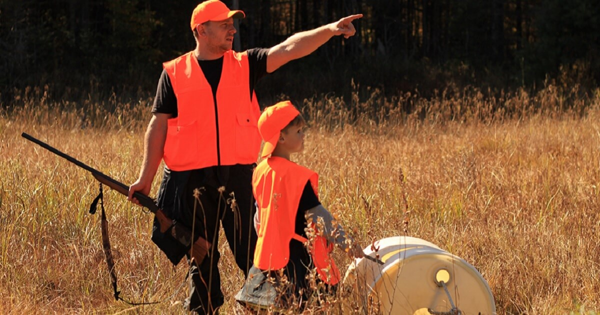 A man and his son in the field hunting.