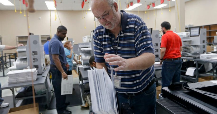 A device is used to straighten ballots before machine counting during a recount at the Broward County Supervisor of Elections office