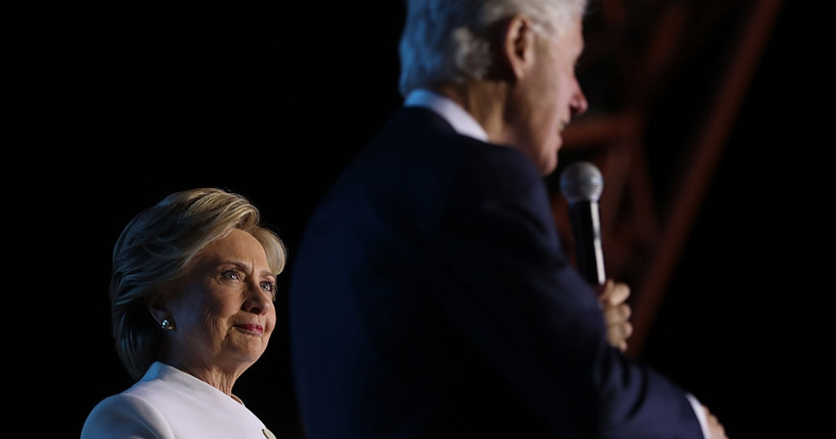 Bill Clinton speaks on stage, while Hillary Clinton looks on