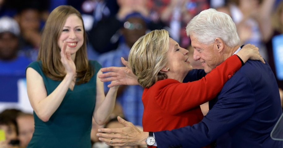 Democratic presidential candidate Hillary Clinton hugs her husband, former President Bill Clinton as their daughter Chelsea Clinton looks on during a campaign rally.