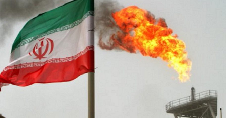 Iranian flag with oil rig in background.