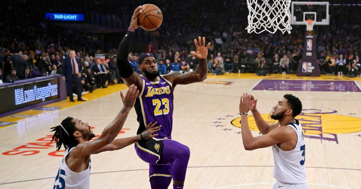 Lakers forward LeBron James shoots as Minnesota Timberwolves guard Derrick Rose, left, and center Karl-Anthony Towns defend during their game Wednesday in Los Angeles.
