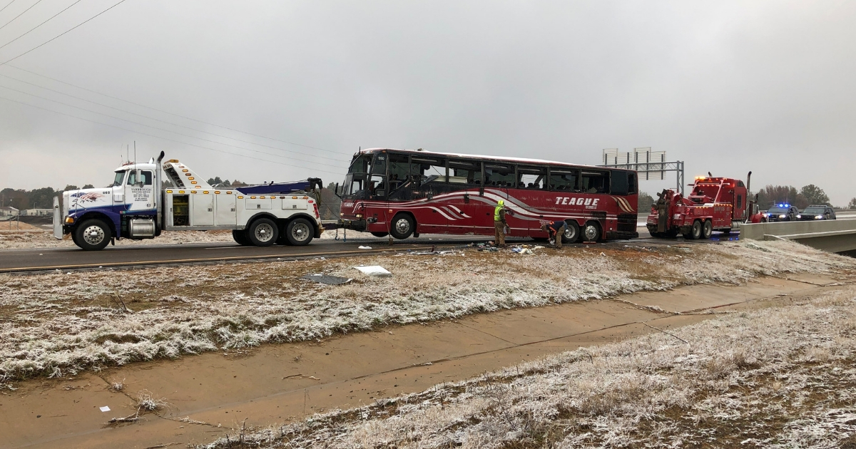 A tour bus is towed away Wednesday after it overturned on an icy highway in northern Mississippi.