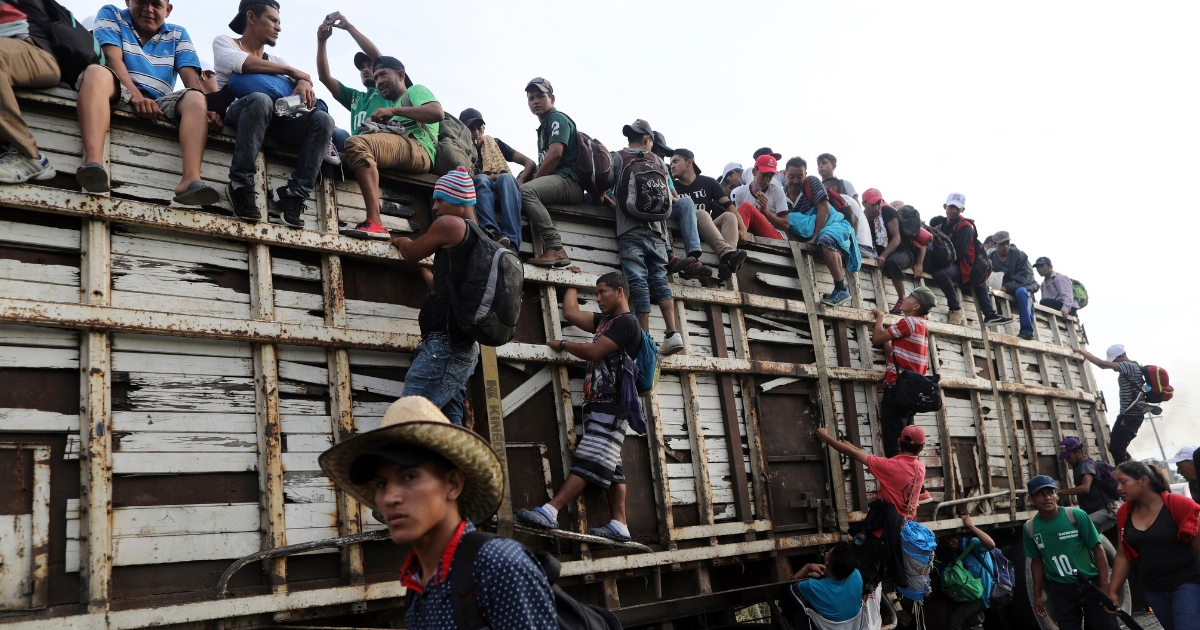 Members of a U.S.-bound migrant caravan board a truck on the road after Mexico's federal police briefly blocked them outside the town of Arriaga, Oct. 27, 2018.