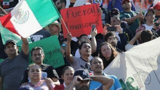 Mexican protesters demonstrate Sunday against the caravan of Central American migrants, some of whom arrived in Tijuana.