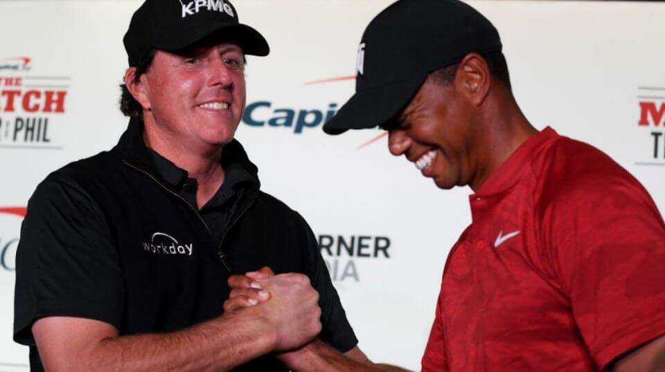 Phil Mickelson and Tiger Woods shake hands while laughing