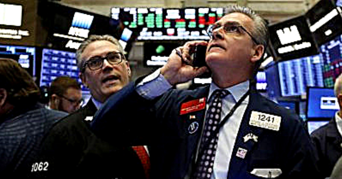 Traders Eric Schumacher, left, and Richard Deviccaro work on the floor of the New York Stock Exchange on Thursday.