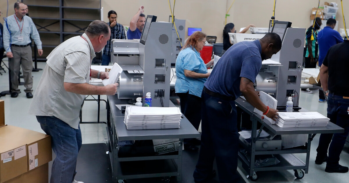 Elections staff load ballots into machine as recounting begins at the Broward County Supervisor of Elections Office on Nov. 11, 2018, in Lauderhill, Florida.