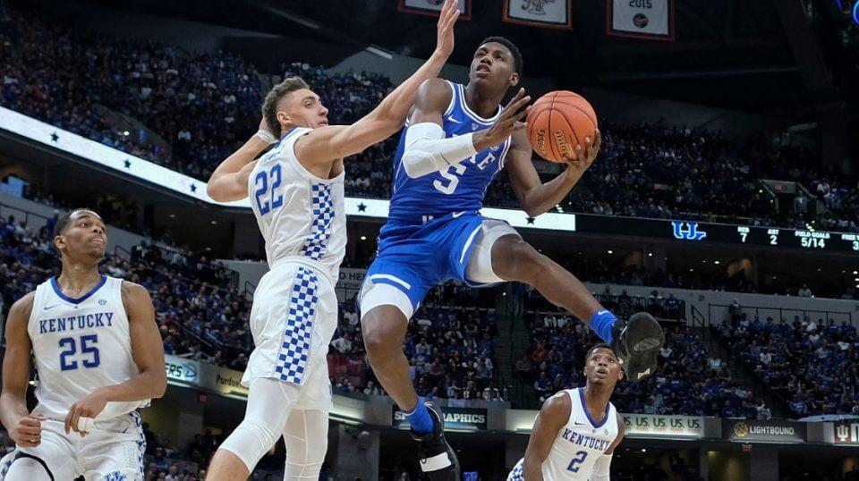 Duke forward RJ Barrett (5) shoots around Kentucky forward Reid Travis (22) during the Champions Classic on Tuesday in Indianapolis.