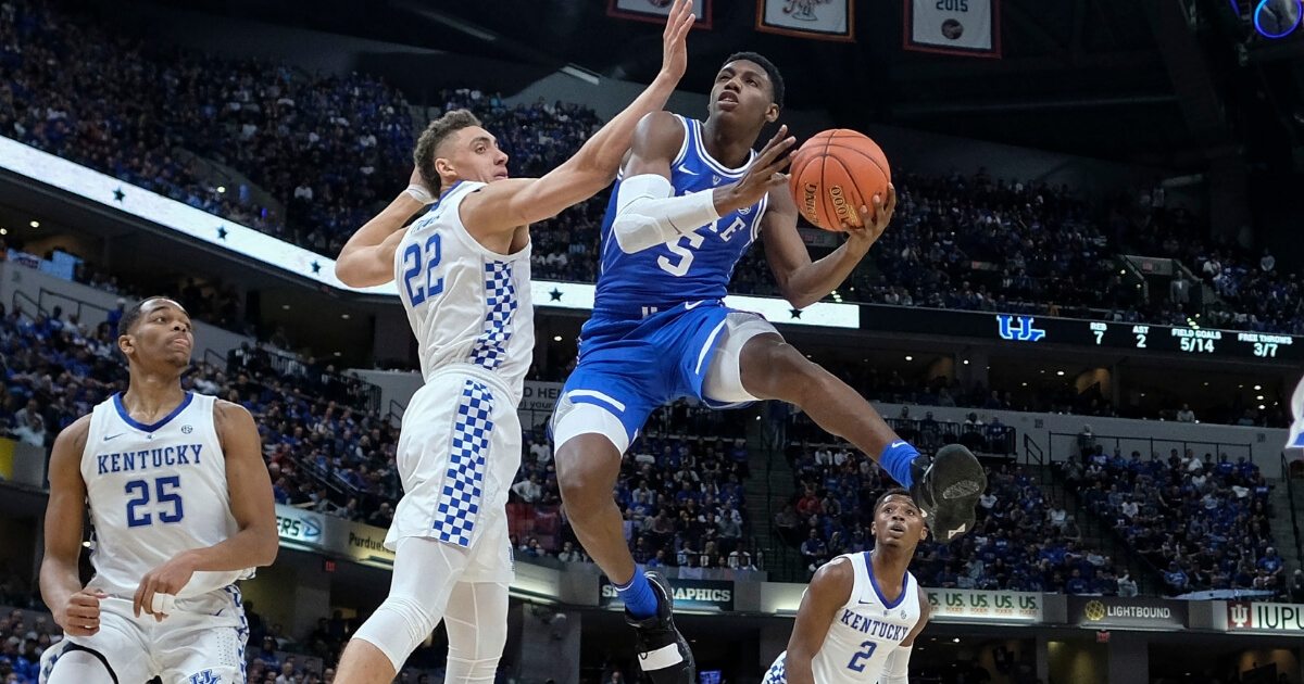 Duke forward RJ Barrett (5) shoots around Kentucky forward Reid Travis (22) during the Champions Classic on Tuesday in Indianapolis.