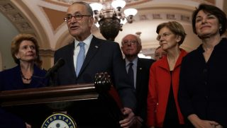 Sen. Chuck Schumer stands in front of several Senate Democrats