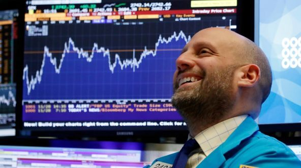 A trader smiles as he works on the floor of the New York Stock Exchange