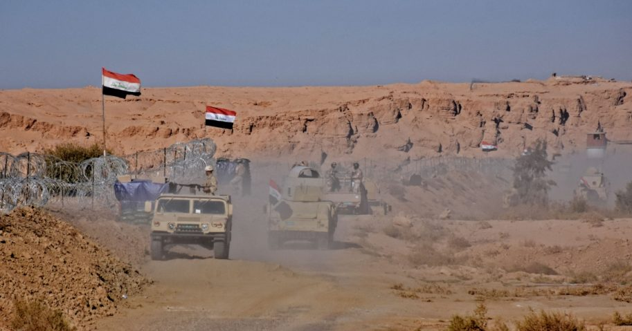 Iraqi forces gather near the al-Qaim border crossing between Syria and Iraq