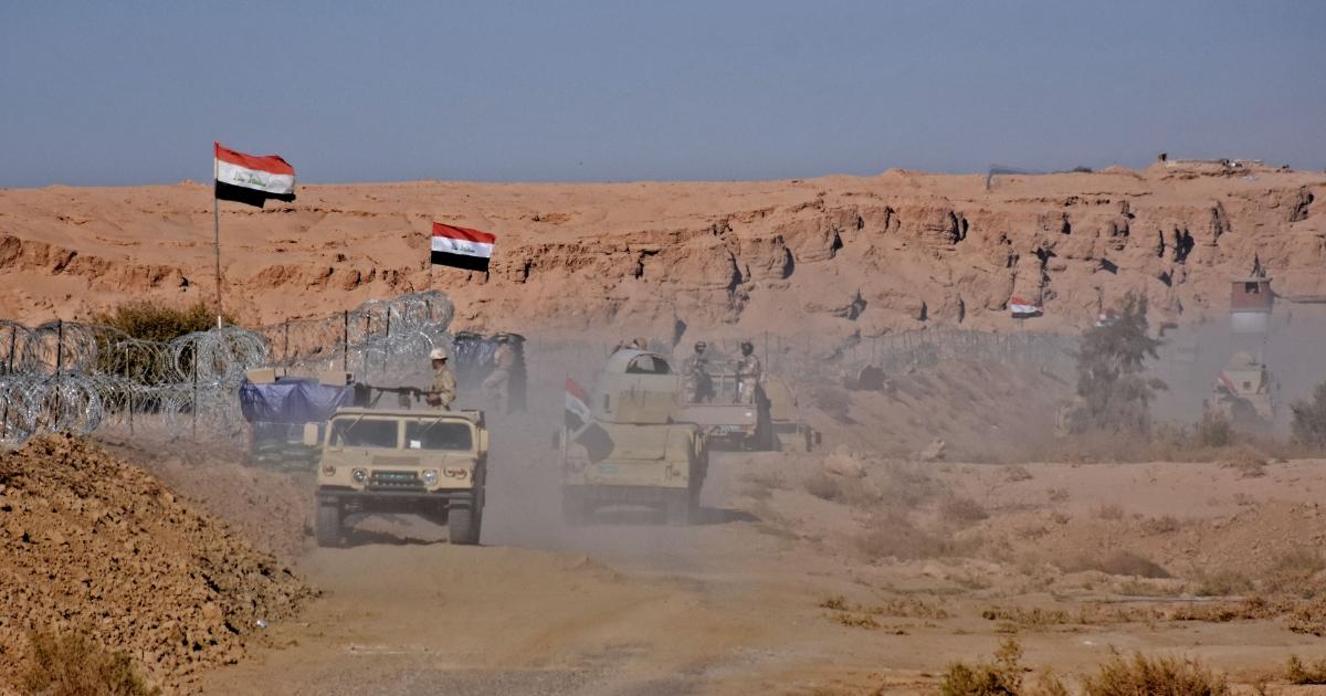 Iraqi forces gather near the al-Qaim border crossing between Syria and Iraq