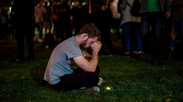 A man rests his head on his hands during a vigil to pay tribute to the victims of a shooting in Thousand Oaks, California